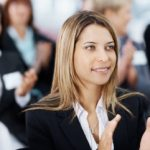 Beautiful young business woman applauding along with colleagues during a seminar